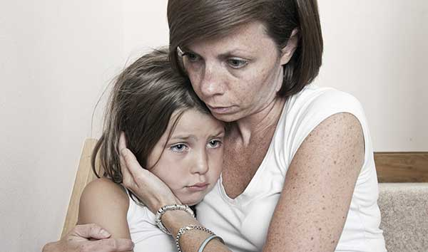 Worried mum hugging upset daughter