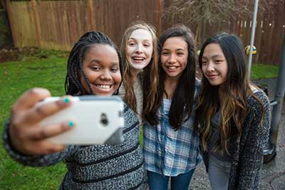 Group of girls smiling, posing for a selfie
